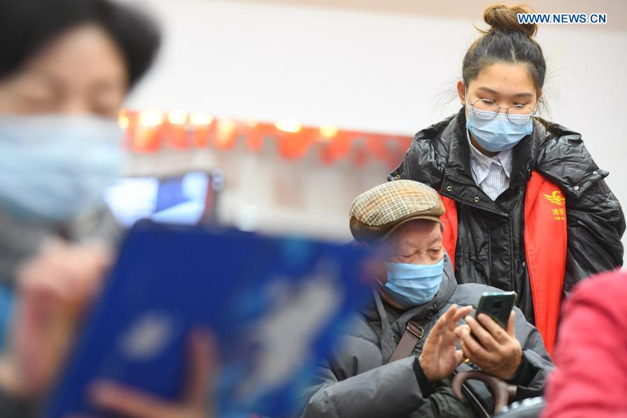 A volunteer teaches the use of smartphone to an elder at Xiajiachong community in Tianxin District of Changsha City, central China's Hunan Province, Jan. 12, 2021. The community has invited volunteers to teach the use of smartphone to elders, helping them keep pace with modern society. (Xinhua/Chen Zeguo)