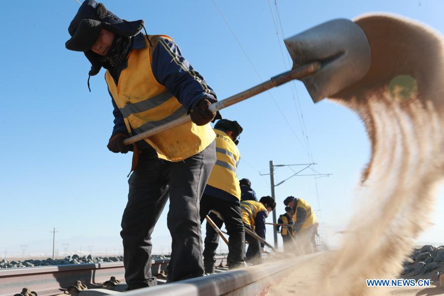 Railway workers clean sand at Kazak Autonomous County of Aksay in northwest China's Gansu Province, Jan. 12, 2021. The Dunhuang railway, which fully opened in December 2019, intersects with existing railways, including the Lanzhou-Qinghai Railway, Qinghai-Tibet Railway and Lanzhou-Xinjiang Railway, to form the first circular railway network in the northwestern region. Among them, the section from Yangguan to Shashangou is located in Shazaoyuan, a place known for its strong crosswind in the Kazak Autonomous County of Aksay. Sand would bury the track from time to time, posing a serious threat to railway operation. The 14 employees of Subei railway maintenance branch of Jiayuguan section of China Railway Lanzhou Bureau Group Co., Ltd. undertake the task of maintenance, among which the most common work is to clean up the sand burying rail connection parts and sleepers. They have to set off at 5 o'clock in the morning to do the job with the lowest temperature in the Gobi Desert dropping to below minus 30 degrees Celsius in winter. It is also common to work for 6 hours at ordinary times and 10 hours under extreme weather condition. (Xinhua/Du Zheyu)