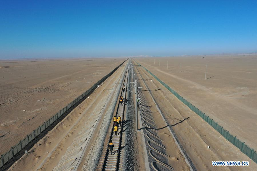 Aerial photo taken on Jan. 12, 2021 shows railway workers cleaning sand at Kazak Autonomous County of Aksay in northwest China's Gansu Province. The Dunhuang railway, which fully opened in December 2019, intersects with existing railways, including the Lanzhou-Qinghai Railway, Qinghai-Tibet Railway and Lanzhou-Xinjiang Railway, to form the first circular railway network in the northwestern region. Among them, the section from Yangguan to Shashangou is located in Shazaoyuan, a place known for its strong crosswind in the Kazak Autonomous County of Aksay. Sand would bury the track from time to time, posing a serious threat to railway operation. The 14 employees of Subei railway maintenance branch of Jiayuguan section of China Railway Lanzhou Bureau Group Co., Ltd. undertake the task of maintenance, among which the most common work is to clean up the sand burying rail connection parts and sleepers. They have to set off at 5 o'clock in the morning to do the job with the lowest temperature in the Gobi Desert dropping to below minus 30 degrees Celsius in winter. It is also common to work for 6 hours at ordinary times and 10 hours under extreme weather condition. (Xinhua/Du Zheyu)