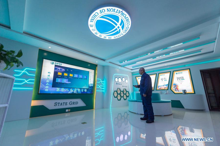 Wang Shaoting adjusts the display screen at the multi-functional exhibition hall in the Beiji Power Supply Station in Beiji Village of Mohe City, northeast China's Heilongjiang Province, Jan. 12, 2021. Beiji Village, located in Mohe City, the northernmost city in China, could only rely on small diesel generators for power supply before 2007. After connecting to the State Grid, Beiji Village set up the northernmost power supply station in China, the Beiji Power Supply Station. Director Lyu Jiansheng and meter reader Wang Shaoting are the only two staff members of the station which is in charge of more than 20 kilometers of overhead lines and 70 kilometers of buried cable lines around it. The temperature in the village often drops to below minus 40 degrees Celsius, and they patrol along the line every once in a while. In 2020, the power supply station renovated multi-functional exhibition hall and canteen, purchased kitchenware and installed bathroom.