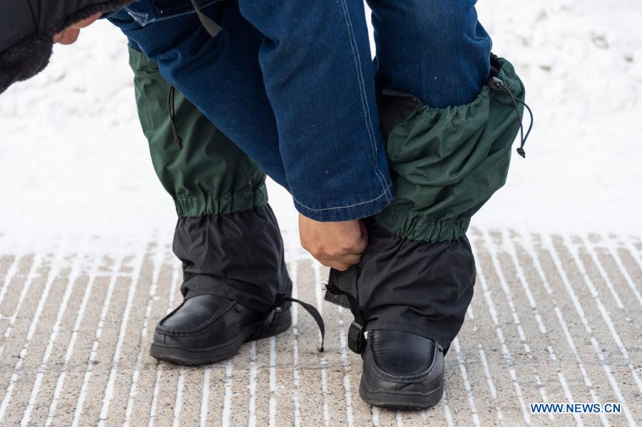 Lyu Jiansheng covers his trouser legs to protect against snow before conducting power line patrol in the forest in Beiji Village of Mohe City, northeast China's Heilongjiang Province, Jan. 12, 2021. Beiji Village, located in Mohe City, the northernmost city in China, could only rely on small diesel generators for power supply before 2007. After connecting to the State Grid, Beiji Village set up the northernmost power supply station in China, the Beiji Power Supply Station. Director Lyu Jiansheng and meter reader Wang Shaoting are the only two staff members of the station which is in charge of more than 20 kilometers of overhead lines and 70 kilometers of buried cable lines around it. The temperature in the village often drops to below minus 40 degrees Celsius, and they patrol along the line every once in a while. In 2020, the power supply station renovated multi-functional exhibition hall and canteen, purchased kitchenware and installed bathroom.