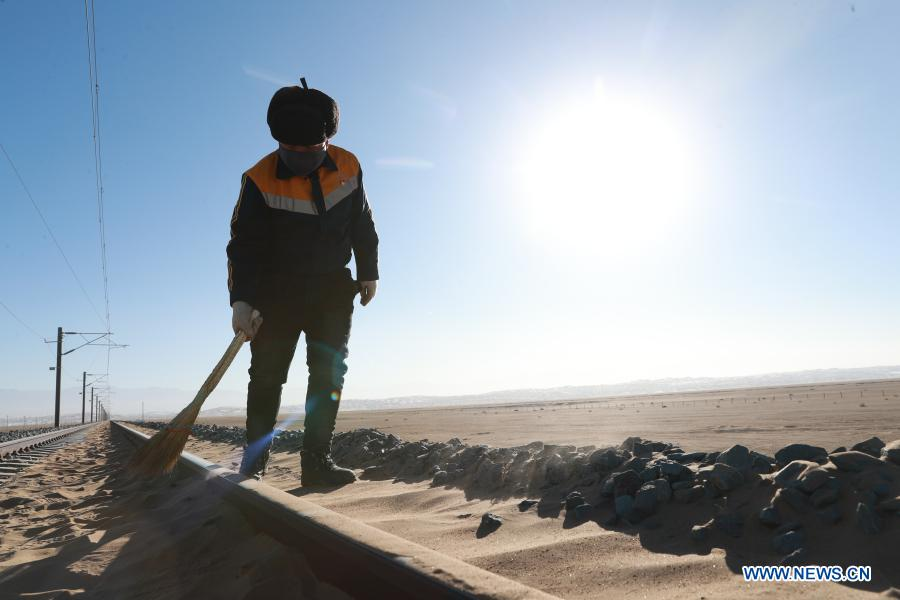 A railway worker cleans sand at Kazak Autonomous County of Aksay in northwest China's Gansu Province, Jan. 12, 2021. The Dunhuang railway, which fully opened in December 2019, intersects with existing railways, including the Lanzhou-Qinghai Railway, Qinghai-Tibet Railway and Lanzhou-Xinjiang Railway, to form the first circular railway network in the northwestern region. Among them, the section from Yangguan to Shashangou is located in Shazaoyuan, a place known for its strong crosswind in the Kazak Autonomous County of Aksay. Sand would bury the track from time to time, posing a serious threat to railway operation. The 14 employees of Subei railway maintenance branch of Jiayuguan section of China Railway Lanzhou Bureau Group Co., Ltd. undertake the task of maintenance, among which the most common work is to clean up the sand burying rail connection parts and sleepers. They have to set off at 5 o'clock in the morning to do the job with the lowest temperature in the Gobi Desert dropping to below minus 30 degrees Celsius in winter. It is also common to work for 6 hours at ordinary times and 10 hours under extreme weather condition. (Xinhua/Du Zheyu)