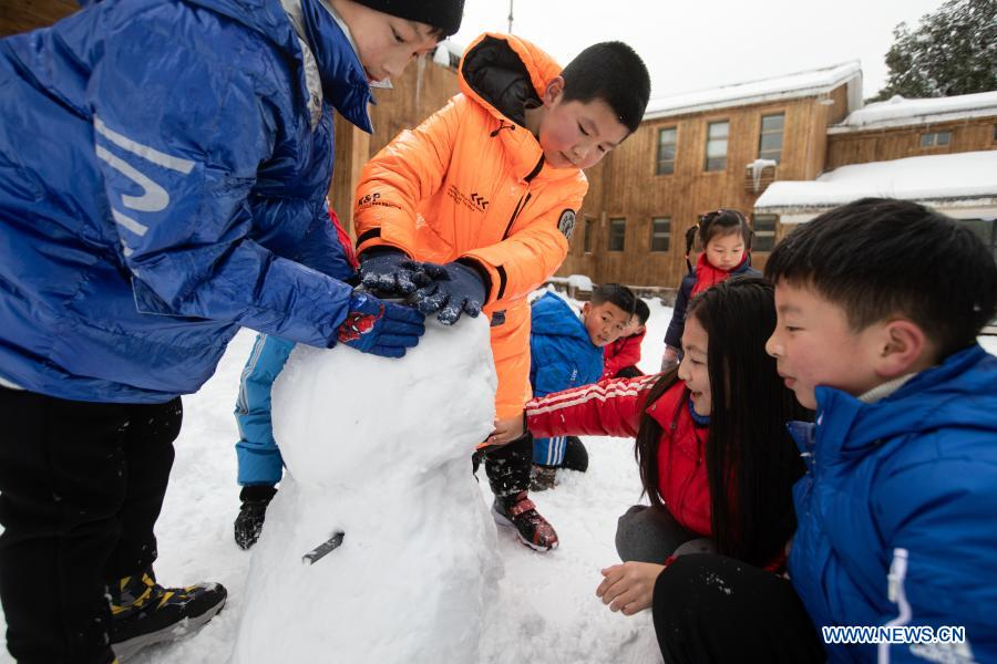 Students from Huchangbao Primary School build a snowman at a camp in Longcanggou National Forest Park in Yingjing County, southwest China's Sichuan Province, Jan. 13, 2021. Recent years Yingjing County has organized a series of educational activities in Longcanggou National Forest Park to boost local education in natural environment. (Xinhua/Liu Mengqi)