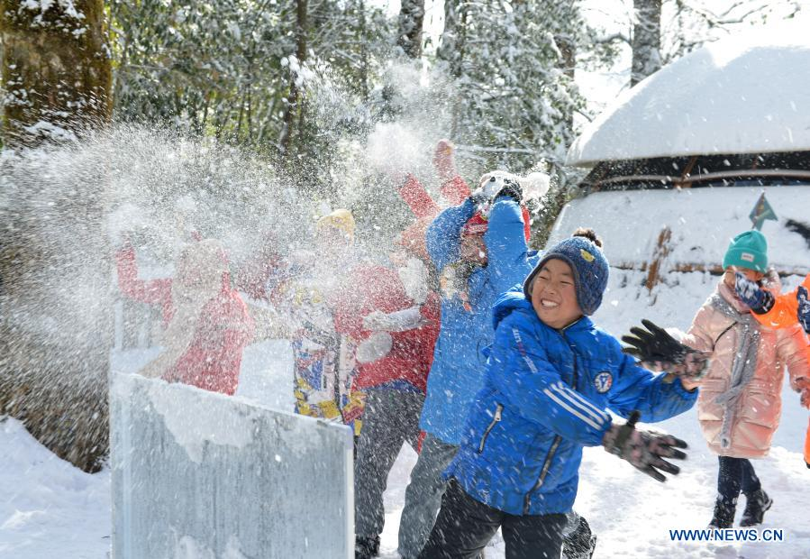 Students from Huchangbao Primary School have snow fight at a camp in Longcanggou National Forest Park in Yingjing County, southwest China's Sichuan Province, Jan. 13, 2021. Recent years Yingjing County has organized a series of educational activities in Longcanggou National Forest Park to boost local education in natural environment. (Xinhua/Liu Mengqi)