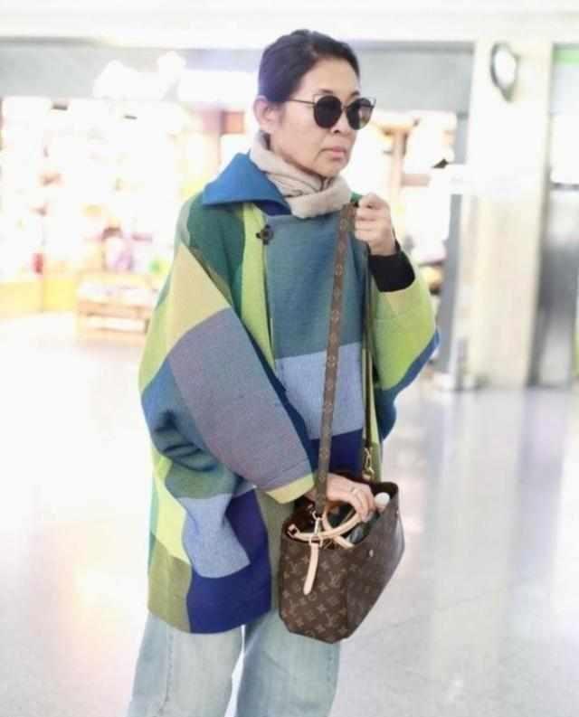 60岁倪萍也玩时尚,穿斗篷上衣配牛仔裤走机场,LV包包时髦又高级