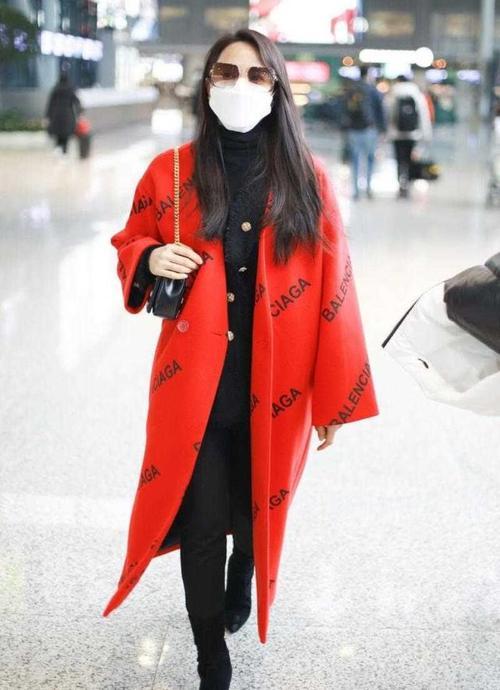 伊能静穿红大衣走机场,踩高跟长靴,打扮这么时髦不像老人