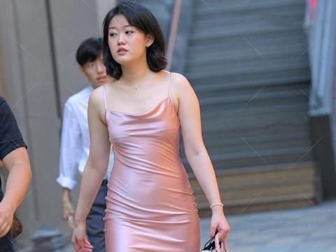 成熟女生一袭连衣裙,粉色丝绸材质,穿着有个人特色