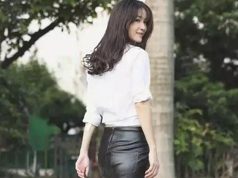 小姐姐一件白色的衬衫搭黑色皮质半裙,优雅地展示出她美丽的双腿