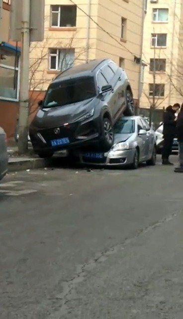 网友爆料:长春一小区内,一私家车倒车骑上另一辆私家车。 这...