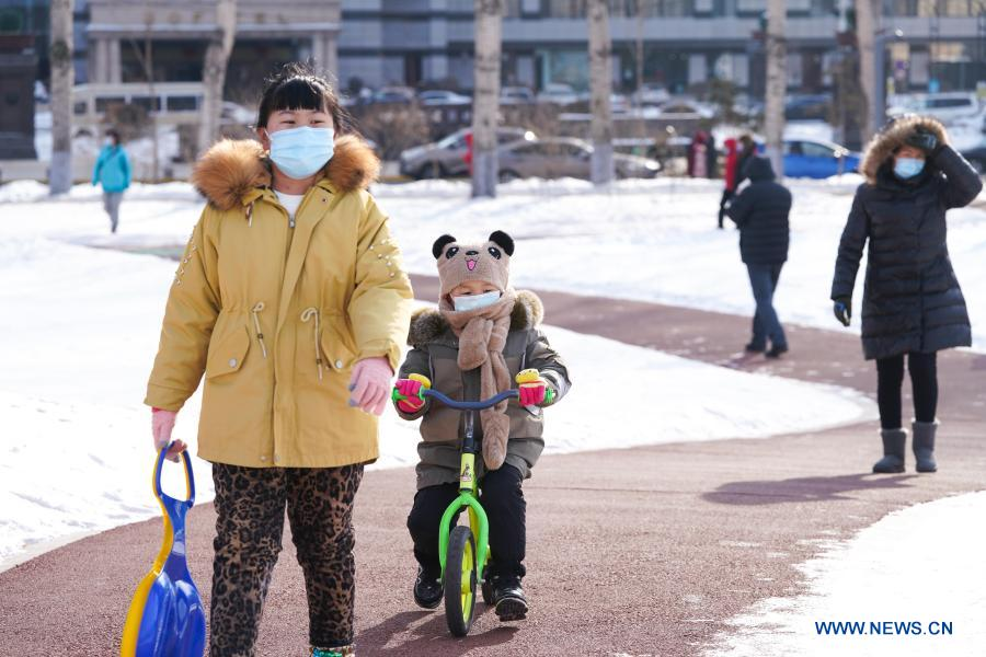 People have fun in the Xiangjiang Park in Harbin City of northeast China's Heilongjiang Province, Feb. 18, 2021. Yutian sub-district of the Limin development zone and Jianshelu sub-district of Hulan District, both in Harbin, have been downgraded to areas of low COVID-19 infection risk on Thursday. Harbin has so far cleared all areas with medium and high COVID-19 infection risks. (Xinhua/Wang Song)