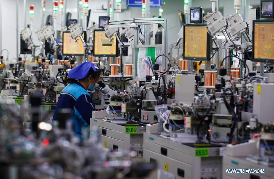An employee works at an electronics company in Sihong, east China's Jiangsu Province, Feb. 18, 2021. Enterprises all over the country started operation again on Thursday as the Spring Festival holiday came to an end. (Photo by Xu Changliang/Xinhua)