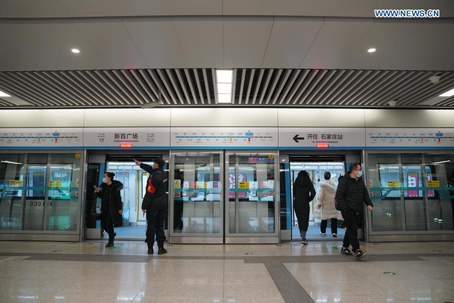 Passengers get on and off a train at Xinbaiguangchang Station in Shijiazhuang, north China's Hebei Province, Feb. 19, 2021. Shijiazhuang resumed all-around subway operation with COVID-19 prevention measures on Friday. (Xinhua/Mu Yu)