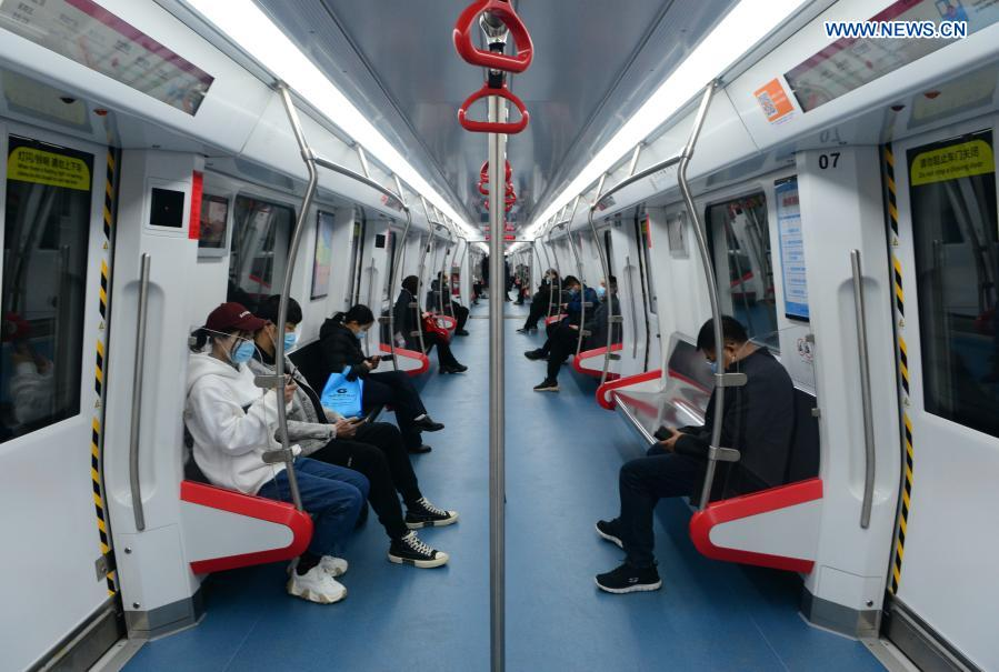 Passengers wearing face masks take a train of subway line 1 in Shijiazhuang, north China's Hebei Province, Feb. 19, 2021. Shijiazhuang resumed all-around subway operation with COVID-19 prevention measures on Friday. (Xinhua/Jin Haoyuan)