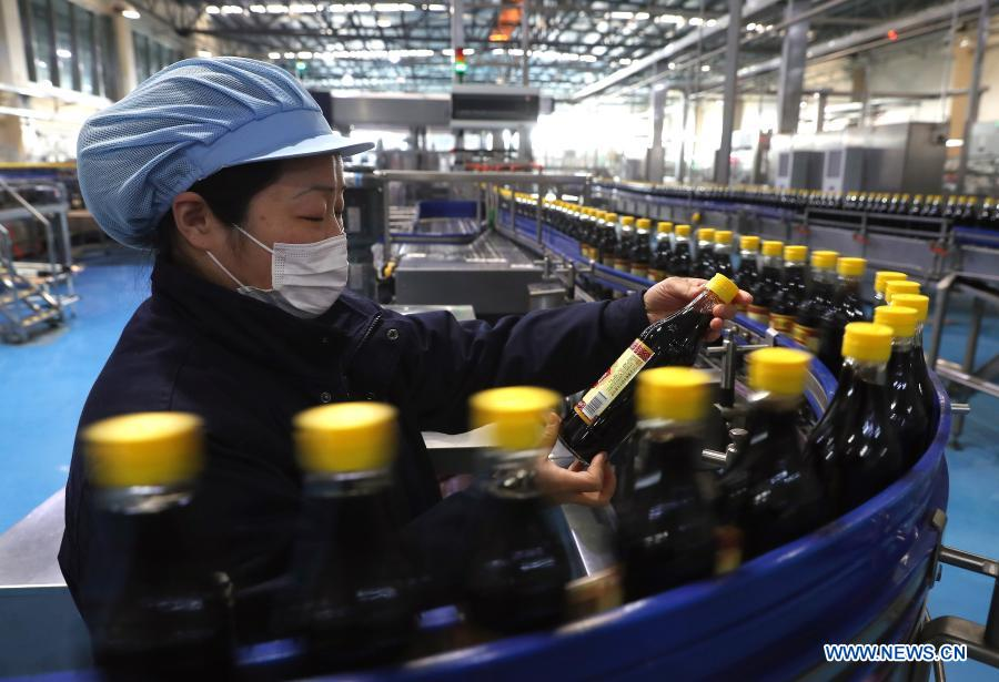 A staff worker examines bottles of vinegar in Zhenjiang, east China's Jiangsu Province, Feb. 18, 2021. Enterprises all over the country started operation again on Thursday as the Spring Festival holiday came to an end. (Photo by Xin Yi/Xinhua)