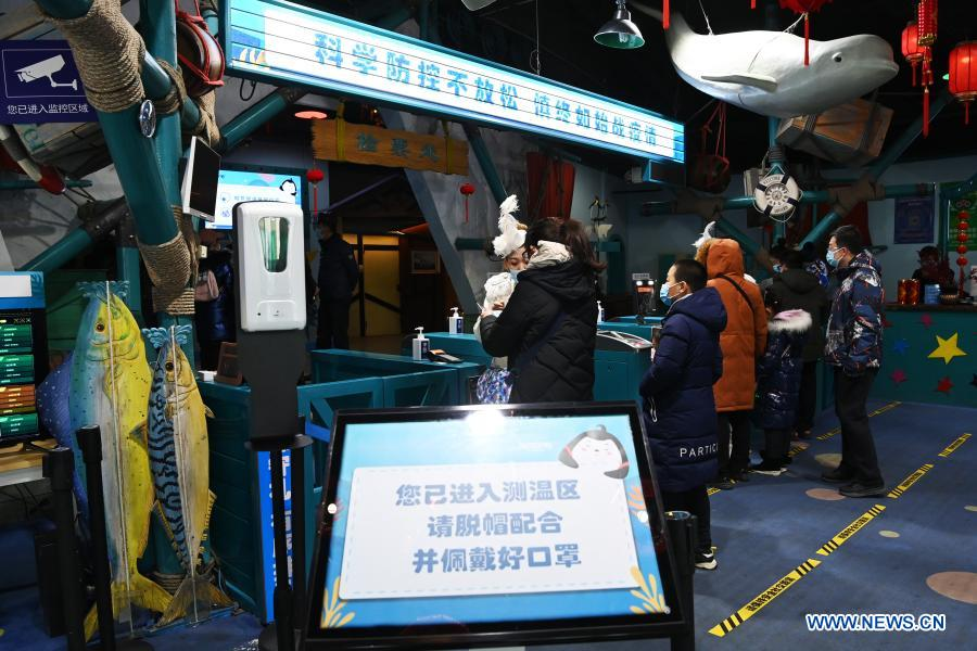 Visitors have their body temperature checked at an entrance to Harbin Polarland in Harbin, capital of northeast China's Heilongjiang Province, Feb. 21, 2021. The Harbin Polarland resumed its operation with sufficient COVID-19 prevention and control measures on Sunday. (Xinhua/Wang Jianwei)