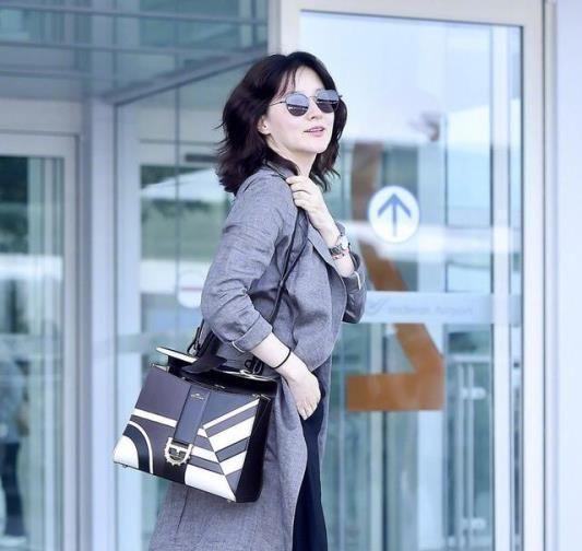 李英爱身穿灰色长外套搭配阔腿裤,休闲造型洒脱率性