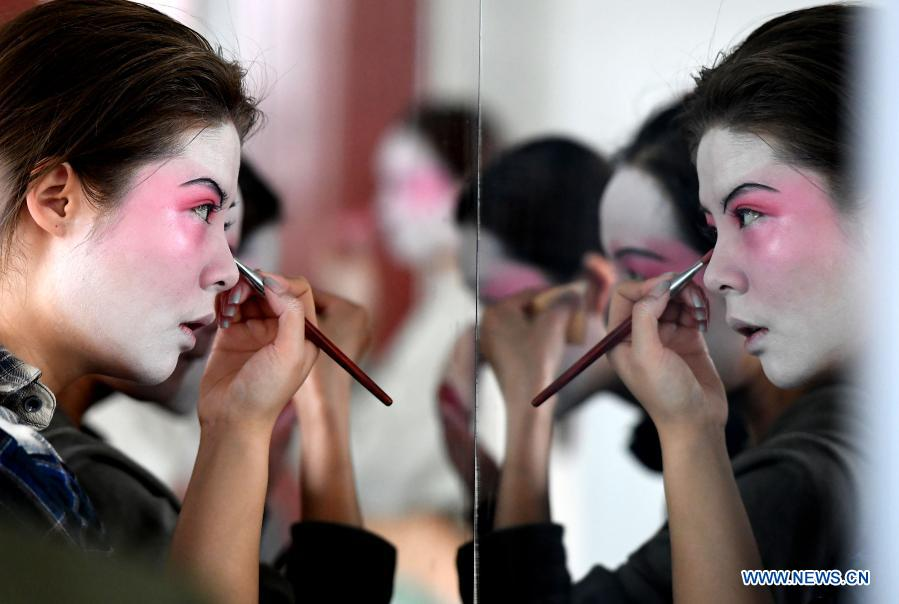 Dancers put on makeup at Zhengzhou Song and Dance Theater in Zhengzhou, central China's Henan Province, Feb. 20, 2021. Fourteen dancers from Zhengzhou Song and Dance Theater have been very busy since the dancing they performed went viral online. The performance, named Banquet of Tang Palace, was staged at the Spring Festival gala of Henan Province. Brilliantly choreographed and acted, the dancing has almost brought ancient dancing figurines of the Tang Dynasty (618-907) alive. The performance Banquet of Tang Palace, inspired by the dancing figurines displayed at a museum, tells a story about the life of female musicians during the Tang Dynasty.