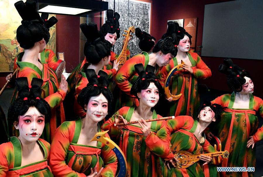 Dancers pose for photos during the recording of a program at Henan Museum in Zhengzhou, central China's Henan Province, Feb. 20, 2021. Fourteen dancers from Zhengzhou Song and Dance Theater have been very busy since the dancing they performed went viral online. The performance, named Banquet of Tang Palace, was staged at the Spring Festival gala of Henan Province. Brilliantly choreographed and acted, the dancing has almost brought ancient dancing figurines of the Tang Dynasty (618-907) alive. The performance Banquet of Tang Palace, inspired by the dancing figurines displayed at a museum, tells a story about the life of female musicians during the Tang Dynasty.