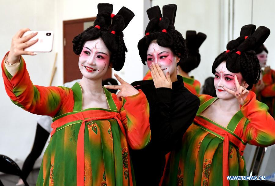 Dancers take selfies at Zhengzhou Song and Dance Theater in Zhengzhou, central China's Henan Province, Feb. 20, 2021. Fourteen dancers from Zhengzhou Song and Dance Theater have been very busy since the dancing they performed went viral online. The performance, named Banquet of Tang Palace, was staged at the Spring Festival gala of Henan Province. Brilliantly choreographed and acted, the dancing has almost brought ancient dancing figurines of the Tang Dynasty (618-907) alive. The performance Banquet of Tang Palace, inspired by the dancing figurines displayed at a museum, tells a story about the life of female musicians during the Tang Dynasty.
