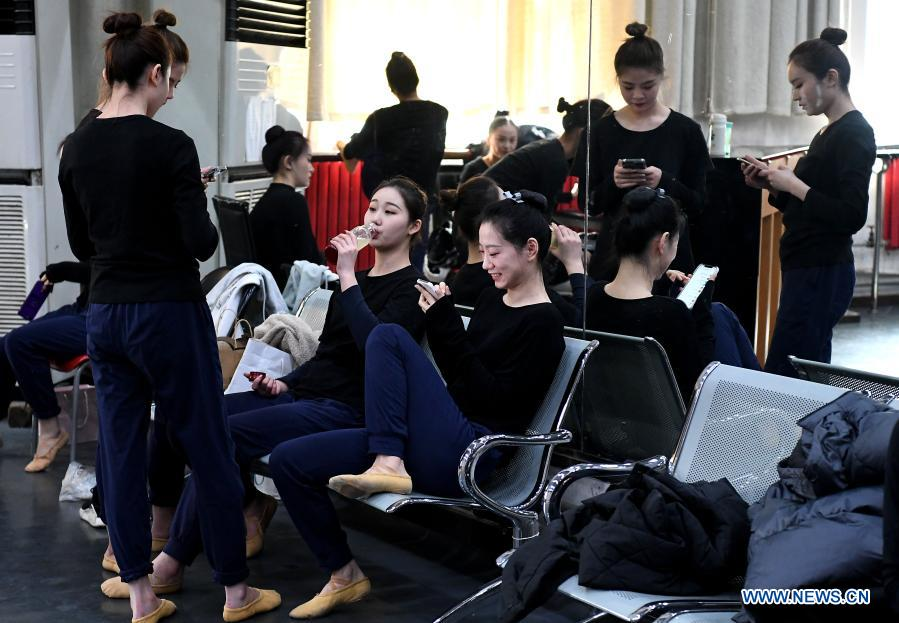 Dancers take a break at Zhengzhou Song and Dance Theater in Zhengzhou, central China's Henan Province, Feb. 20, 2021. Fourteen dancers from Zhengzhou Song and Dance Theater have been very busy since the dancing they performed went viral online. The performance, named Banquet of Tang Palace, was staged at the Spring Festival gala of Henan Province. Brilliantly choreographed and acted, the dancing has almost brought ancient dancing figurines of the Tang Dynasty (618-907) alive. The performance Banquet of Tang Palace, inspired by the dancing figurines displayed at a museum, tells a story about the life of female musicians during the Tang Dynasty.