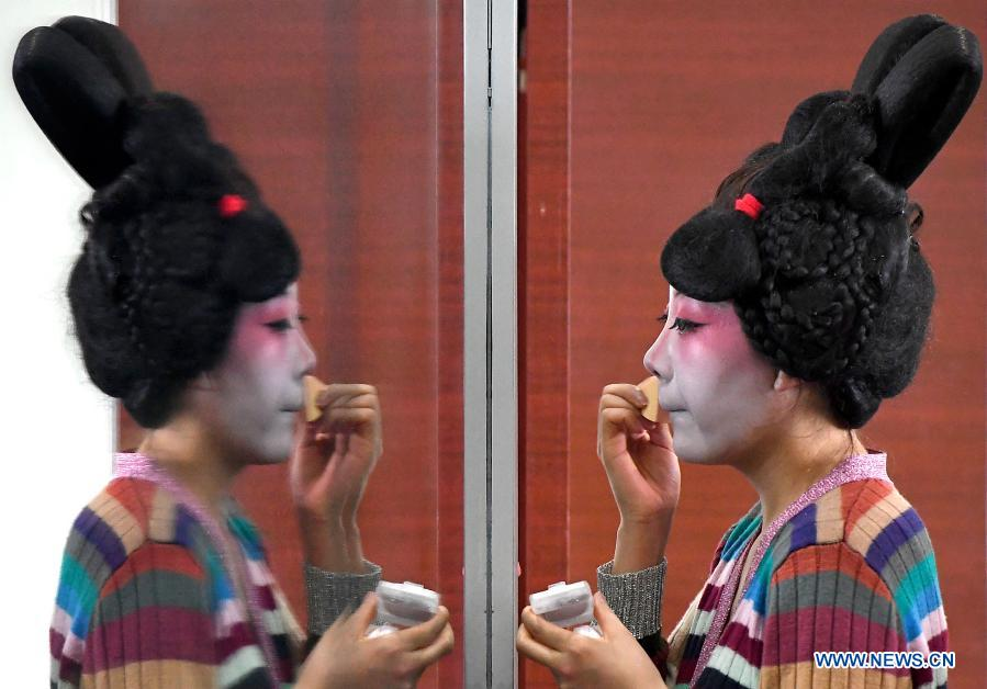 A dancer puts on makeup at Zhengzhou Song and Dance Theater in Zhengzhou, central China's Henan Province, Feb. 20, 2021. Fourteen dancers from Zhengzhou Song and Dance Theater have been very busy since the dancing they performed went viral online. The performance, named Banquet of Tang Palace, was staged at the Spring Festival gala of Henan Province. Brilliantly choreographed and acted, the dancing has almost brought ancient dancing figurines of the Tang Dynasty (618-907) alive. The performance Banquet of Tang Palace, inspired by the dancing figurines displayed at a museum, tells a story about the life of female musicians during the Tang Dynasty.