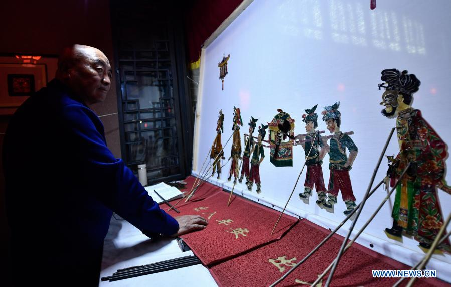 Folk artist Yao Yasheng performs a shadow puppet show at Ping'an District of Haidong, northwest China's Qinghai Province, Feb. 22, 2021. Various cultural events are held here ahead of the upcoming Chinese lantern festival. (Xinhua/Zhang Long)