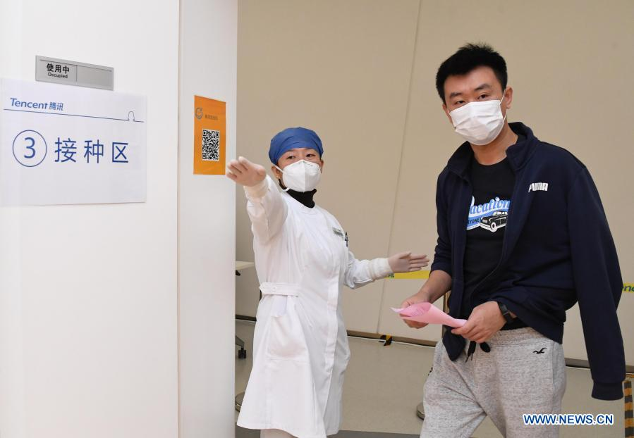 A medical worker (L) guides a man for vaccination at a temporary COVID-19 vaccination site at a company in the ZPark Phase 2 in Haidian District of Beijing, capital of China, Feb. 22, 2021. It is expected to take two days to complete the vaccination of more than 3,800 employees of the enterprise. (Xinhua/Ren Chao)