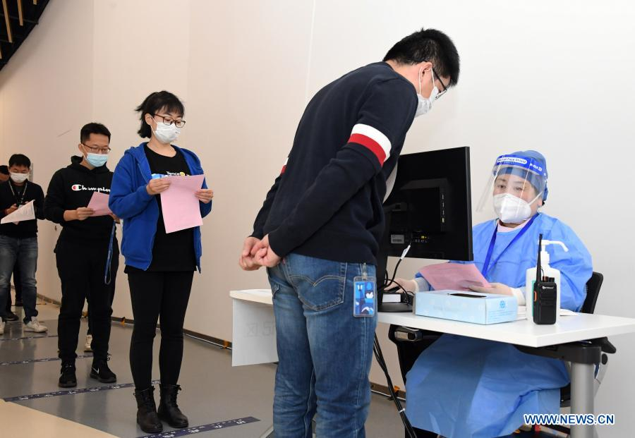 A medical worker (1st R) inputs personal information of the staff members at a temporary COVID-19 vaccination site at a company in the ZPark Phase 2 in Haidian District of Beijing, capital of China, Feb. 22, 2021. It is expected to take two days to complete the vaccination of more than 3,800 employees of the enterprise. (Xinhua/Ren Chao)