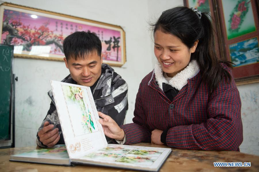 Chang Sheng and his wife look through the photos of their children in Wujing Village of Zhuzhai Town, Funan County of Fuyang, east China's Anhui Province, Feb. 24, 2021. Before returning to work, Chang Sheng, a villager in Wujing Village, and his wife Zhu Chengzhen had a great time with their quadruplets in the village during their Spring Festival holiday. This happy family of six members once experienced a very difficult time a few years ago. In October 2013, Zhu Chengzhen gave birth to the quadruplets in Hefei, capital of Anhui Province. Before the couple could enjoy the joy of being parents for the first time, the reality gave them a hard blow. Due to premature birth, the babies were underweight and were diagnosed as mental retardation. In the following years, in order to treat the quadruplets, Chang and his wife took their children to hospitals in Hefei, Shanghai and other places, with no time to work and no source of income. Before they had children, Chang and his wife had been working outside their hometown for many years. Though they were not rich, they could save some money every year at that time. However, after the quadruplets were born, expenses on medication, rehabilitation and necessities for the children as milk powder and diapers wiped out all of the couple's savings and left them in debt. Soon, Chang Sheng's family was identified as a registered poor household. Thanks to local poverty-relief policies and social support, the couple survived the most difficult years. As their children grew up and got better in health, Chang began to go out for work, while his wife stayed at home to take care of their four children. The family got rid of poverty at the end of 2019, and the quadruplets went to primary school in September 2020. When the children are at school, Zhu Chengzhen also does piecework, such as processing components at home, to earn about 2,000 yuan (about 310 U.S. dollars) a month.