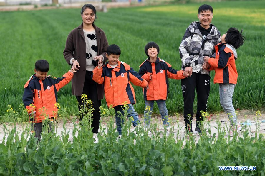 Chang Sheng and his wife take the quadruplets to play in a field in Wujing Village of Zhuzhai Town, Funan County of Fuyang, east China's Anhui Province, Feb. 23, 2021. Before returning to work, Chang Sheng, a villager in Wujing Village, and his wife Zhu Chengzhen had a great time with their quadruplets in the village during their Spring Festival holiday. This happy family of six members once experienced a very difficult time a few years ago. In October 2013, Zhu Chengzhen gave birth to the quadruplets in Hefei, capital of Anhui Province. Before the couple could enjoy the joy of being parents for the first time, the reality gave them a hard blow. Due to premature birth, the babies were underweight and were diagnosed as mental retardation. In the following years, in order to treat the quadruplets, Chang and his wife took their children to hospitals in Hefei, Shanghai and other places, with no time to work and no source of income. Before they had children, Chang and his wife had been working outside their hometown for many years. Though they were not rich, they could save some money every year at that time. However, after the quadruplets were born, expenses on medication, rehabilitation and necessities for the children as milk powder and diapers wiped out all of the couple's savings and left them in debt. Soon, Chang Sheng's family was identified as a registered poor household. Thanks to local poverty-relief policies and social support, the couple survived the most difficult years. As their children grew up and got better in health, Chang began to go out for work, while his wife stayed at home to take care of their four children. The family got rid of poverty at the end of 2019, and the quadruplets went to primary school in September 2020. When the children are at school, Zhu Chengzhen also does piecework, such as processing components at home, to earn about 2,000 yuan (about 310 U.S. dollars) a month.