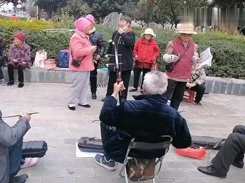 云南文山某广场上,大爷拉二胡大妈唱歌配合默契,简直是天籁之音