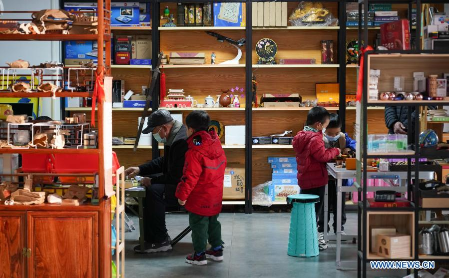 Customers and their children play at a toy shop for the elderly in Beijing, capital of China, Feb. 23, 2021. The toy shop owned by Song Delong, which has about 400 kinds of toys especially for the elderly people, serves not only as a toy shop but a popular leisure and social place for local seniors. (Xinhua/Chen Zhonghao)