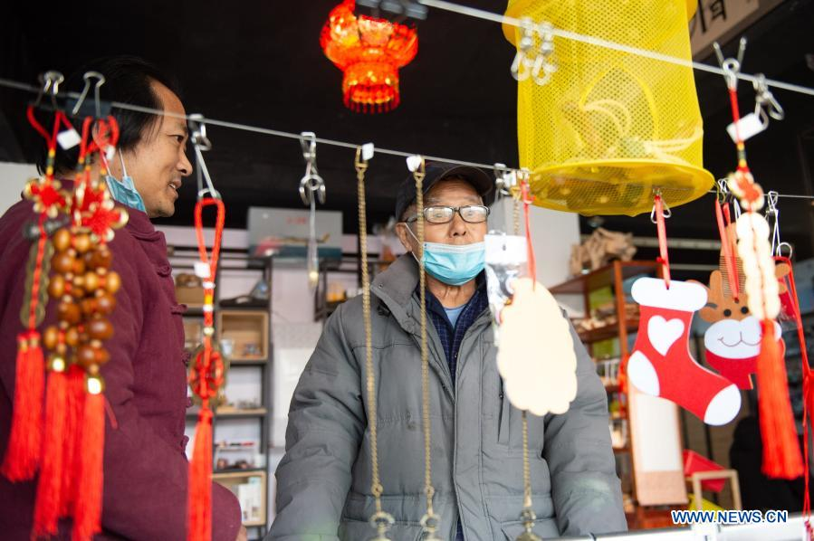 Shop owner Song Delong (L) introduces toys to a customer at his toy shop for the elderly in Beijing, capital of China, Feb. 23, 2021. The toy shop owned by Song Delong, which has about 400 kinds of toys especially for the elderly people, serves not only as a toy shop but a popular leisure and social place for local seniors. (Xinhua/Chen Zhonghao)