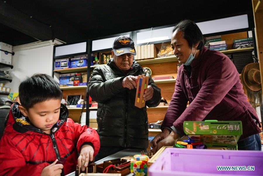 A customer (C) and his grandchild (L) play toys at a toy shop for the elderly in Beijing, capital of China, Feb. 23, 2021. The toy shop owned by Song Delong, which has about 400 kinds of toys especially for the elderly people, serves not only as a toy shop but a popular leisure and social place for local seniors. (Xinhua/Chen Zhonghao)