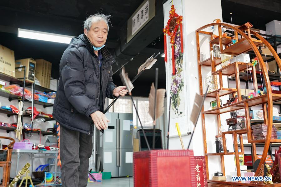 A customer plays Touhu game, or an ancient entertainment that requires players to throw sticks from a set distance into a canister, at a toy shop for the elderly in Beijing, capital of China, Feb. 23, 2021. The toy shop owned by Song Delong, which has about 400 kinds of toys especially for the elderly people, serves not only as a toy shop but a popular leisure and social place for local seniors. (Xinhua/Chen Zhonghao)