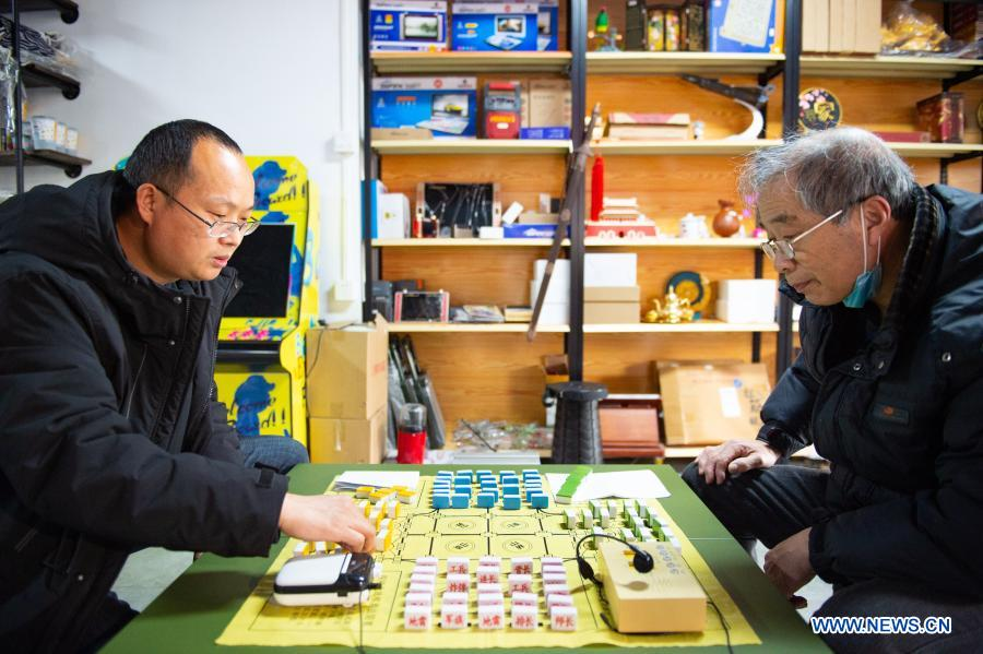 Customers play Junqi, a kind of chess game, at a toy shop for the elderly in Beijing, capital of China, Feb. 23, 2021. The toy shop owned by Song Delong, which has about 400 kinds of toys especially for the elderly people, serves not only as a toy shop but a popular leisure and social place for local seniors. (Xinhua/Chen Zhonghao)