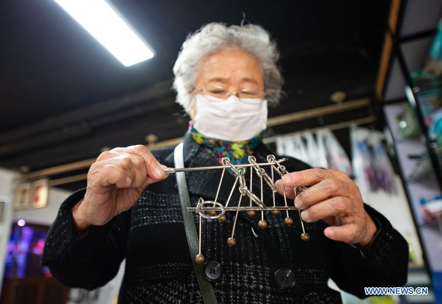 A customer plays a puzzle game at a toy shop for the elderly in Beijing, capital of China, Feb. 23, 2021. The toy shop owned by Song Delong, which has about 400 kinds of toys especially for the elderly people, serves not only as a toy shop but a popular leisure and social place for local seniors. (Xinhua/Chen Zhonghao)