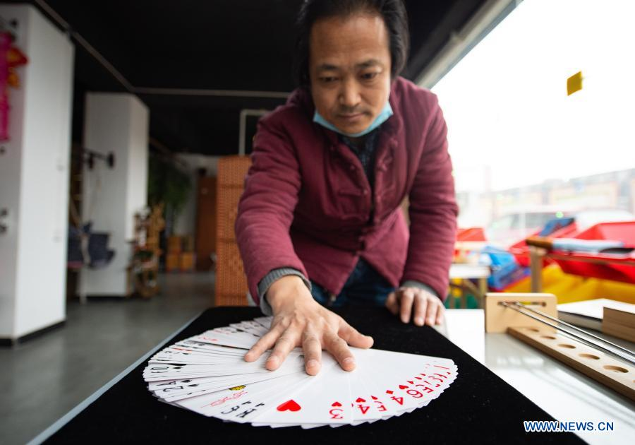 Shop owner Song Delong displays special poker cards for the elderly, which are four times the size of the average one, at his toy shop for the elderly in Beijing, capital of China, Feb. 23, 2021. The toy shop owned by Song Delong, which has about 400 kinds of toys especially for the elderly people, serves not only as a toy shop but a popular leisure and social place for local seniors. (Xinhua/Chen Zhonghao)