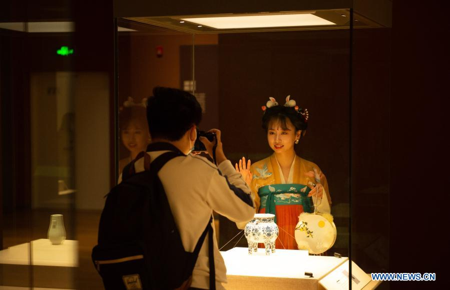 A visitor in traditional Chinese costumes poses for a photo during a night exhibition to celebrate the Lantern Festival at Tsinghua University Art Museum in Beijing, capital of China, Feb. 26, 2021. Various activities were held across China to celebrate the Lantern Festival on Friday, the 15th day of the first month of the Chinese lunar calendar. (Xinhua/Chen Zhonghao)