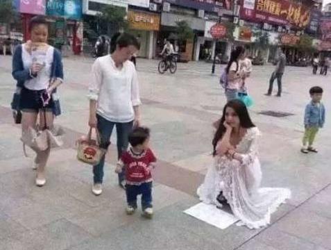 女子身披婚纱上街行乞,引发路人围观,知道真相后哭笑不得