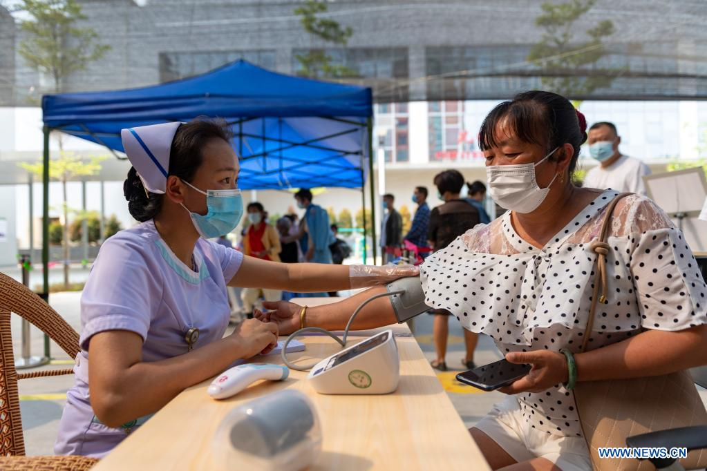A woman measures blood pressure at a COVID-19 vaccination site of Jingcheng Hospital in Ruili City, southwest China's Yunnan Province, April 1, 2021. (Xinhua/Chen Xinbo)