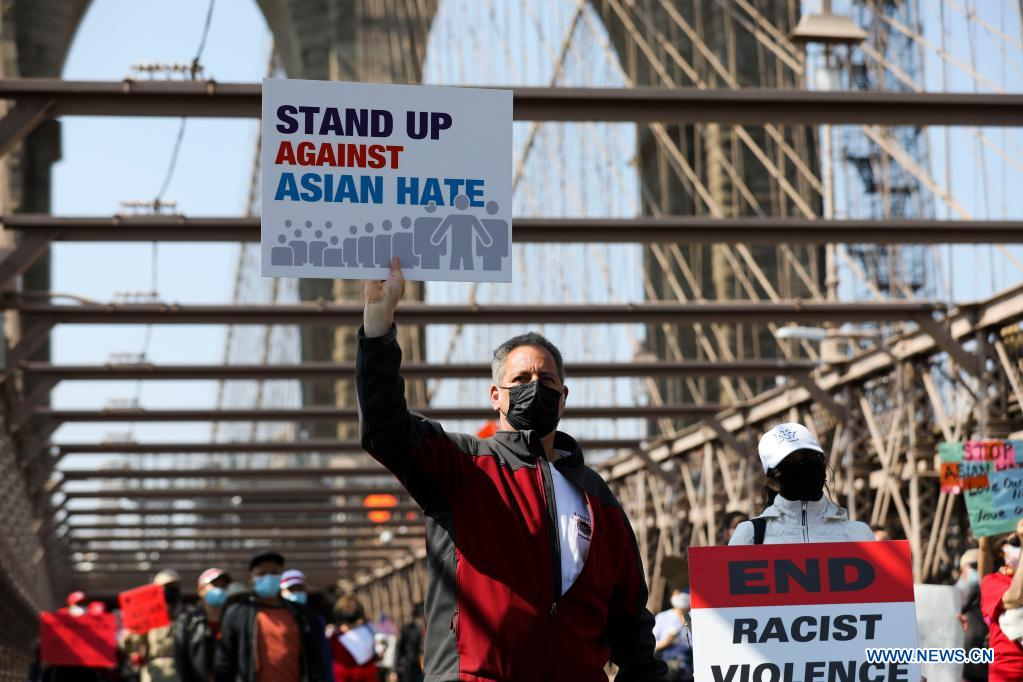 People march to protest against anti-Asian hate crimes on Brooklyn Bridge in New York, the United States, April 4, 2021. A big