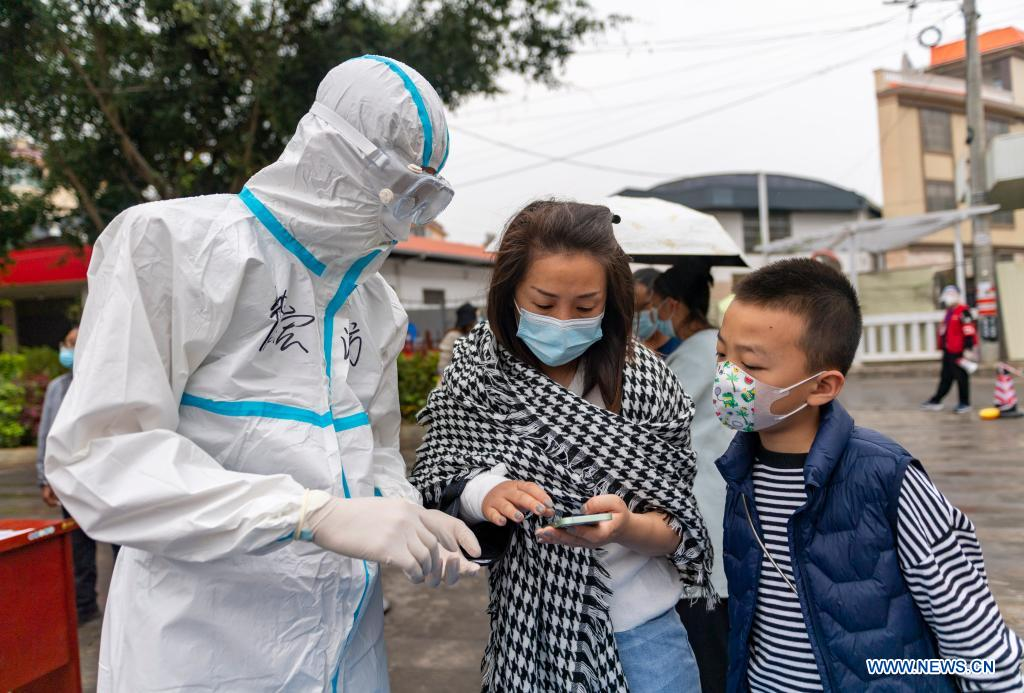 A volunteer guides residents in their registration on mobile phone before receiving nucleic acid testing for COVID-19 at Munao community, Ruili City, southwest China's Yunnan Province, April 6, 2021. Ruili City in southwest China's Yunnan Province on Tuesday launched the second round of nucleic acid testing that includes all residents of the city proper. (Xinhua/Chen Xinbo)