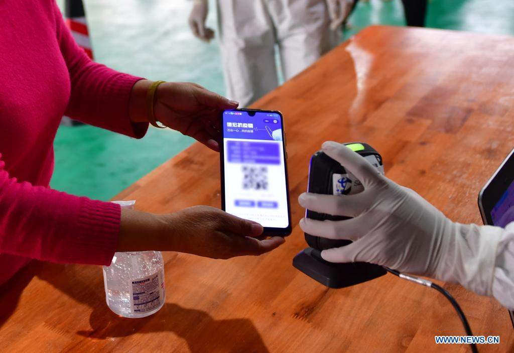A medical worker scans QR code on the mobile phone screen for registration before a resident receives nucleic acid testing for COVID-19 at Munao community, Ruili City, southwest China's Yunnan Province, April 6, 2021. Ruili City in southwest China's Yunnan Province on Tuesday launched the second round of nucleic acid testing that includes all residents of the city proper. (Xinhua/Chen Xinbo)