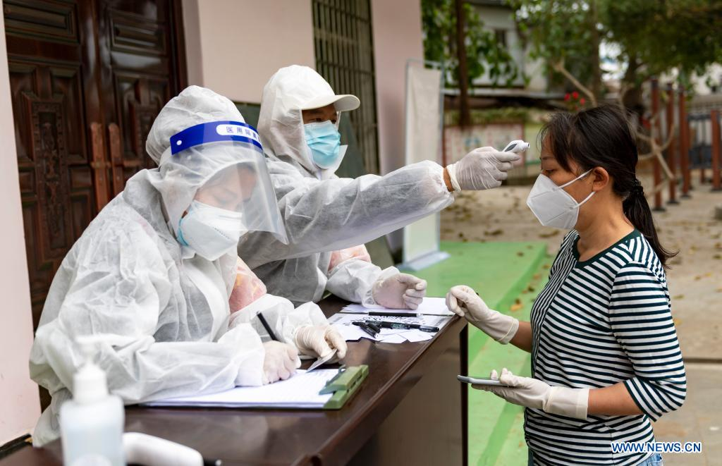 A medical worker measures the body temperature of a resident before she receives nucleic acid testing for COVID-19 at Munao community, Ruili City, southwest China's Yunnan Province, April 6, 2021. Ruili City in southwest China's Yunnan Province on Tuesday launched the second round of nucleic acid testing that includes all residents of the city proper. (Xinhua/Chen Xinbo)