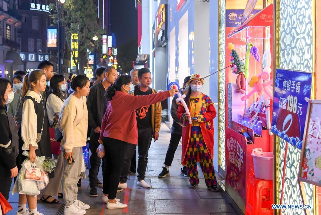 People have fun at a commercial street in Wuhan, central China's Hubei Province, March 29, 2021. Wuhan, once hit hard by COVID-19, has seen its urban life at night return to normal since its lockdown was lifted on April 8, 2020. (Xinhua/Cheng Min)