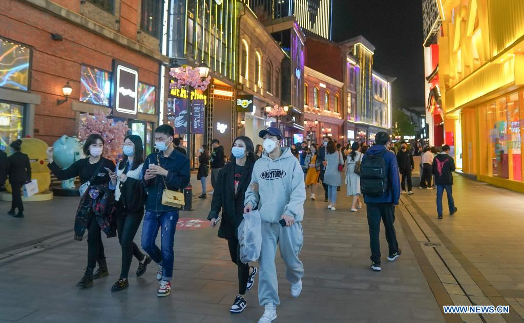 People walk on a commercial street in Wuhan, central China's Hubei Province, March 28, 2021. Wuhan, once hit hard by COVID-19, has seen its urban life at night return to normal since its lockdown was lifted on April 8, 2020. (Xinhua/Cheng Min)
