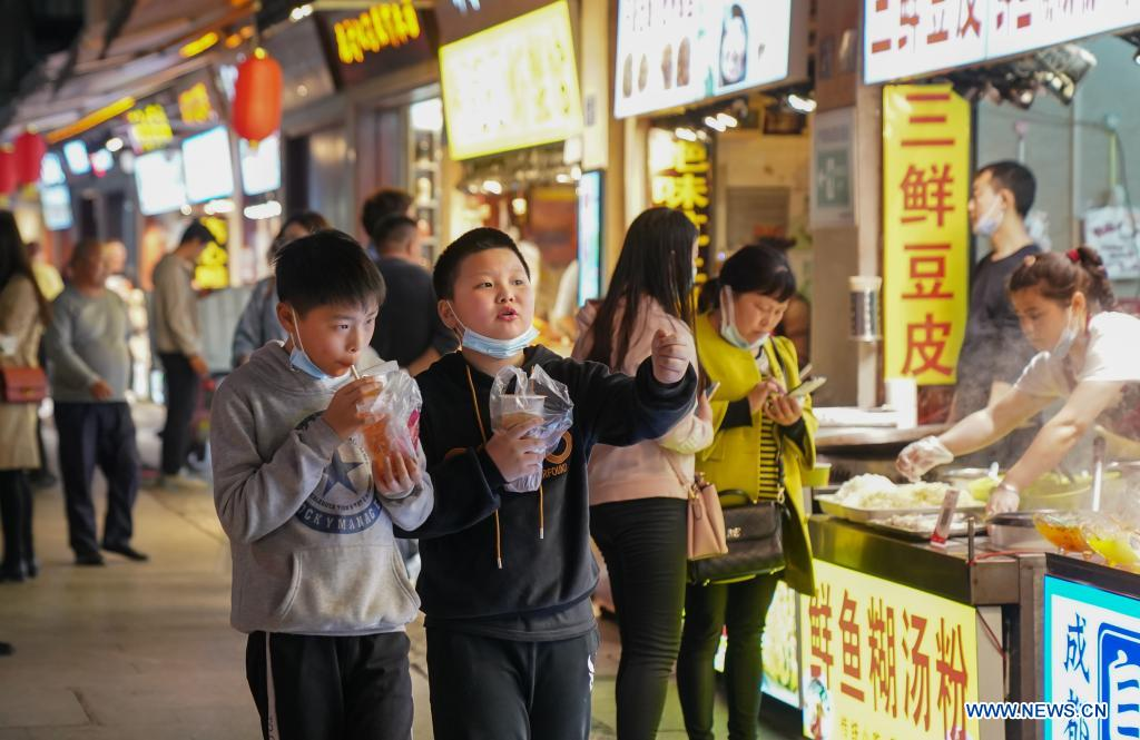 People eat snacks at an alley in Wuhan, central China's Hubei Province, March 28, 2021. Wuhan, once hit hard by COVID-19, has seen its urban life at night return to normal since its lockdown was lifted on April 8, 2020. (Xinhua/Cheng Min)