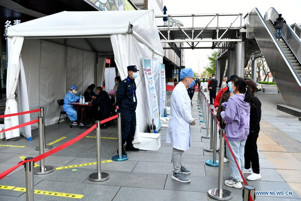 Residents ask details about COVID-19 vaccination at a mobile COVID-19 vaccination site near Xidan business area in downtown Beijing, capital of China, April 7, 2021. Since April 1, Beijing has started to use mobile COVID-19 vaccination vehicles in its four districts to expedite vaccination. The vehicles are equipped with facilities such as computers, refrigerators and air conditioners to ensure the convenience, safety and reliability during the vaccination process. Technologies such as 5G and big data are also employed to manage vaccination with digital means and ensure the traceability of the whole process. (Xinhua/Li Xin)