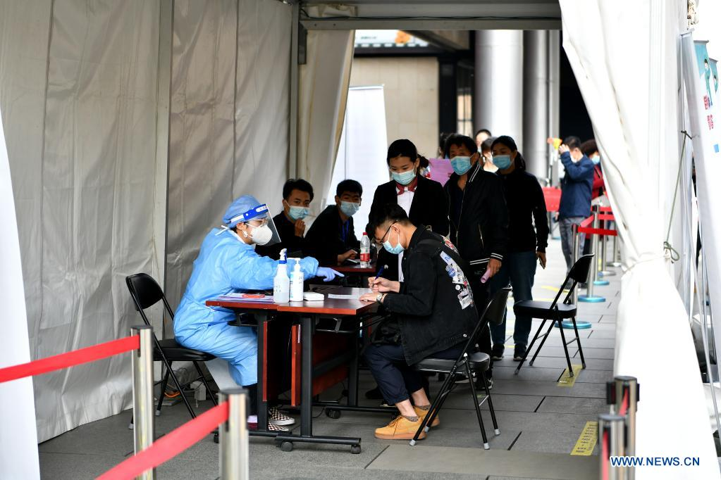 Residents register personal information at a mobile COVID-19 vaccination site near Xidan business area in downtown Beijing, capital of China, April 7, 2021. Since April 1, Beijing has started to use mobile COVID-19 vaccination vehicles in its four districts to expedite vaccination. The vehicles are equipped with facilities such as computers, refrigerators and air conditioners to ensure the convenience, safety and reliability during the vaccination process. Technologies such as 5G and big data are also employed to manage vaccination with digital means and ensure the traceability of the whole process. (Xinhua/Li Xin)